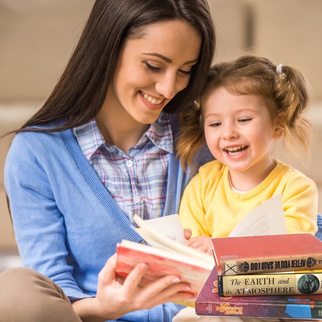 mom reading a book to girl